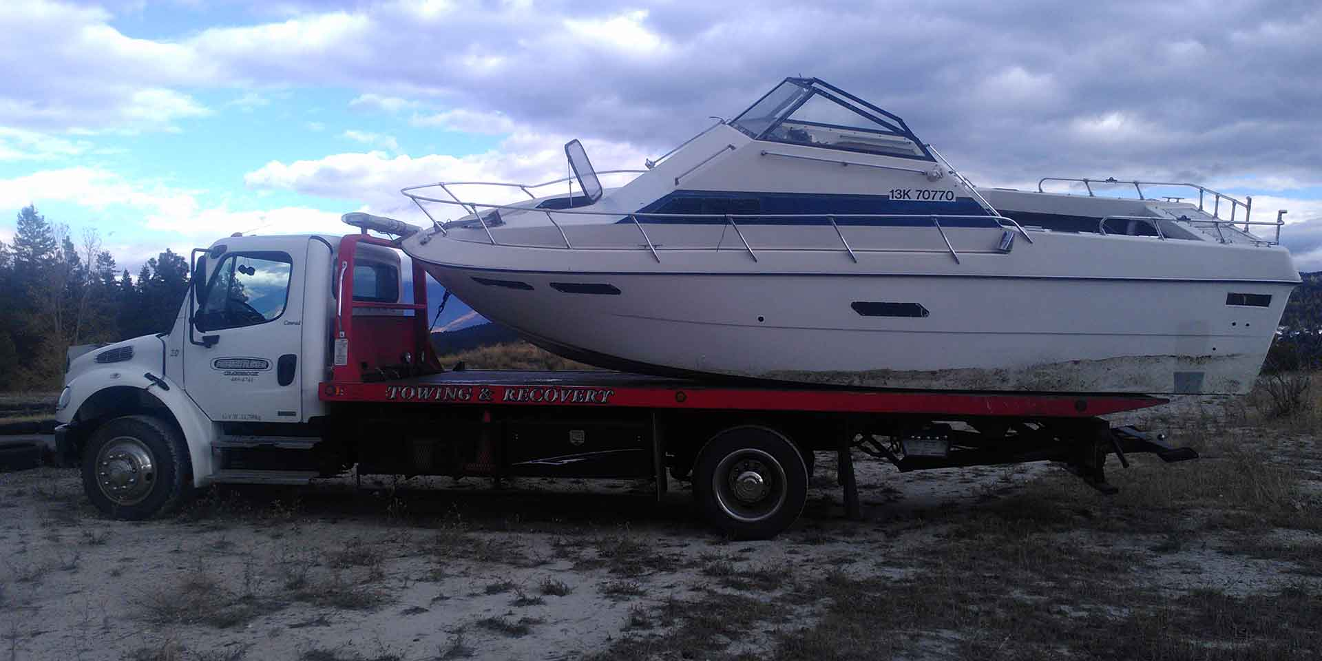 towing and recovery truck towing boat